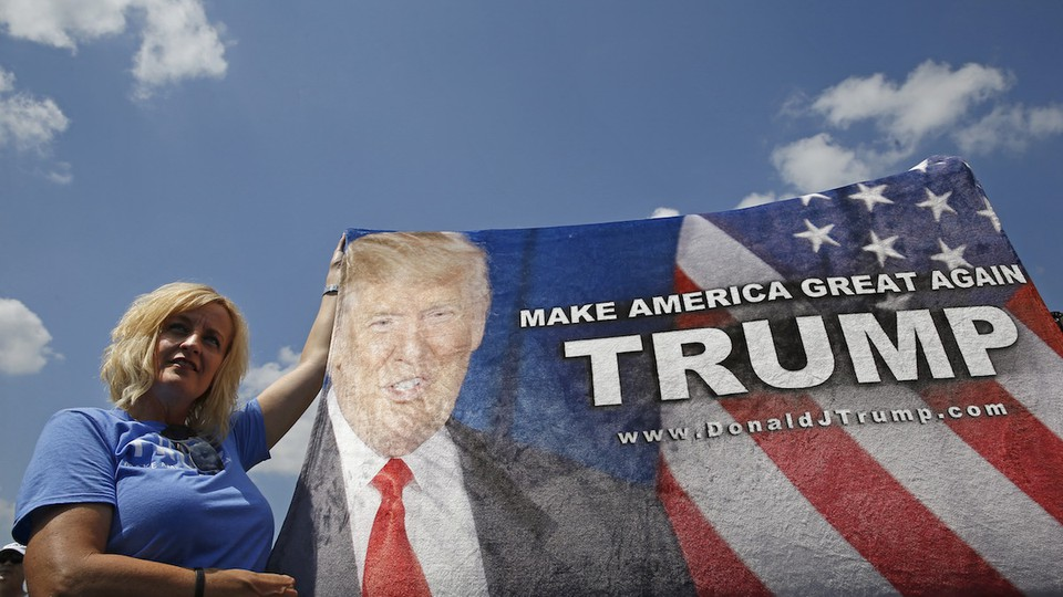 """A white woman with short blond hair, wearing a blue T-shirt, stands outdoors holding up a Trump banner that reads """"Make America Great Again."""""""