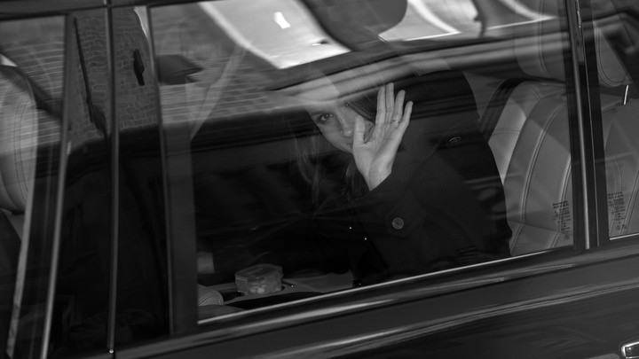 A black-and-white photo of Meghan Markle waving from inside a car.