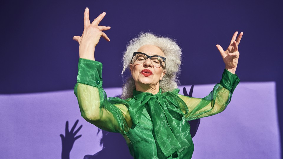 A confident-looking woman holds her arms in the air.