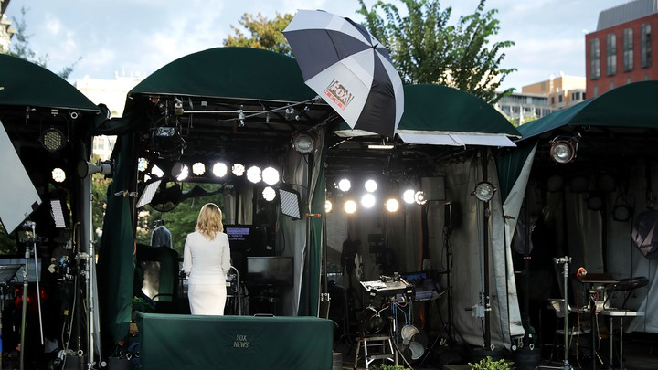 """A Fox News anchor, shot from behind, delivers a broadcast into the camera. She's standing on """"pebble beach,"""" an area of the White House grounds where news networks set up their cameras for live shots."""