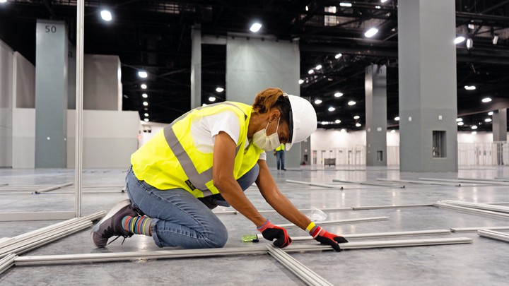 A construction worker kneels on the floor of a large room.