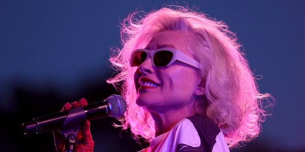 Performer Debbie Harry holds a microphone on stage.