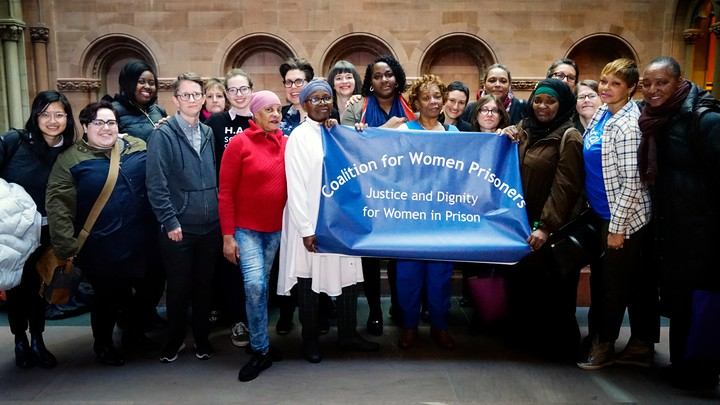 """A group of women hold up a banner reading """"Coalition for Women Prisoners: Justice and Dignity for Women in Prison"""""""