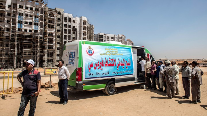 Egyptian workers line up near a van for an examination check-up for Hepatitis C