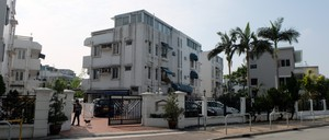 A series of white, three-story apartment buildings surrounded by palm trees and a gate.