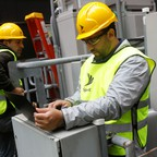 Two men with yellow hard hats surrounded by technology boxes