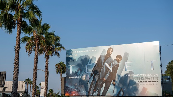A billboard, showing the actor John David Washington, next to palm trees and against a blue sky