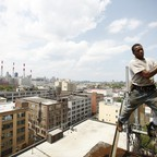 A laborer works on top of a city building
