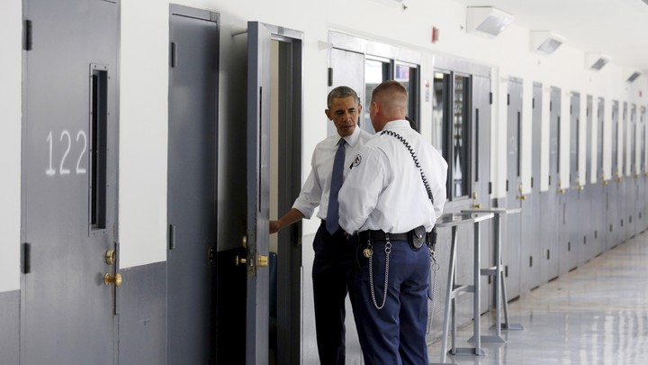 President Obama and a prison guard stand in front of an open door in a bright hallway, looking inside a prison cell.