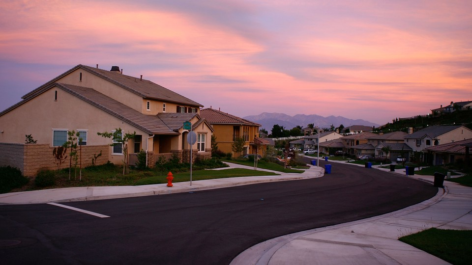 Sunset on a suburban residential block with mountains in the background