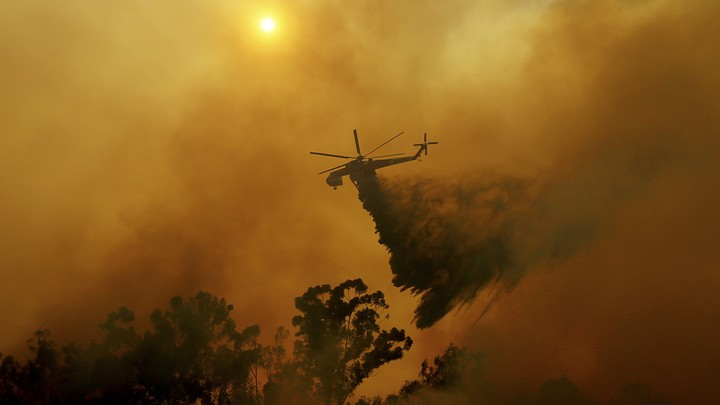 A helicopter drops fire retardant onto a wildfire.