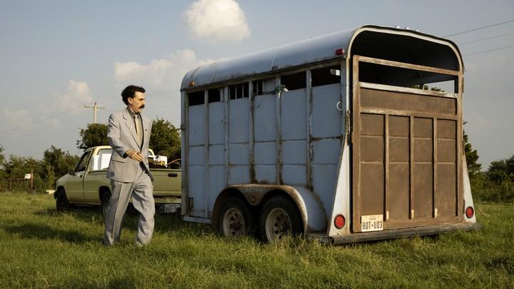 A movie still of Sacha Baron Cohen next to an animal trailer