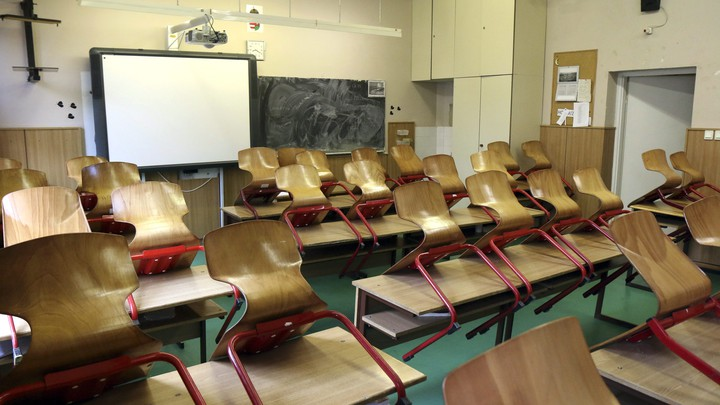 An empty classroom. All the chairs are on top of the desks. There is a Smartboard at the front of the room.