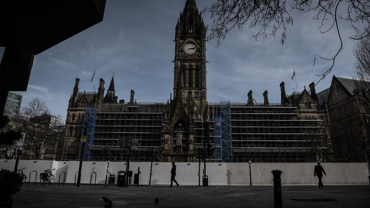 A man walks in front of Manchester Town Hall in the deserted center of Manchester after Prime Minister Boris Johnson imposed a lockdown on England.
