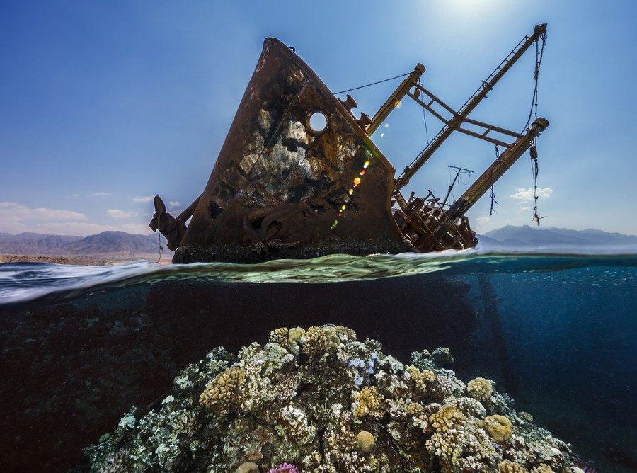 A rusted shipwreck leans as part of it sticks out of the water.
