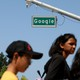 """People walk past a street sign that reads """"Google."""""""