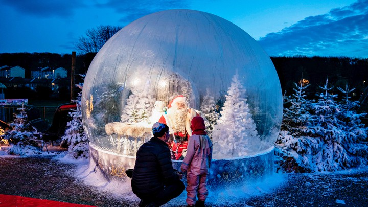 A parent and child stand in front of a blow-up snowglobe.
