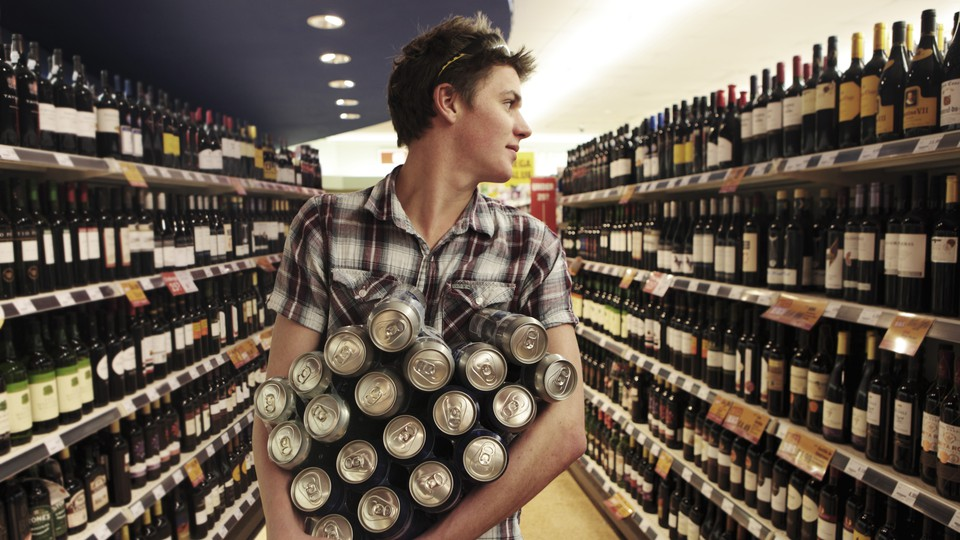 A young man walks down a wine aisle holding many cans.
