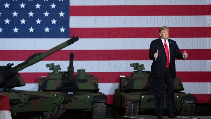 Donald Trump standing in front of tanks and an American-flag backdrop