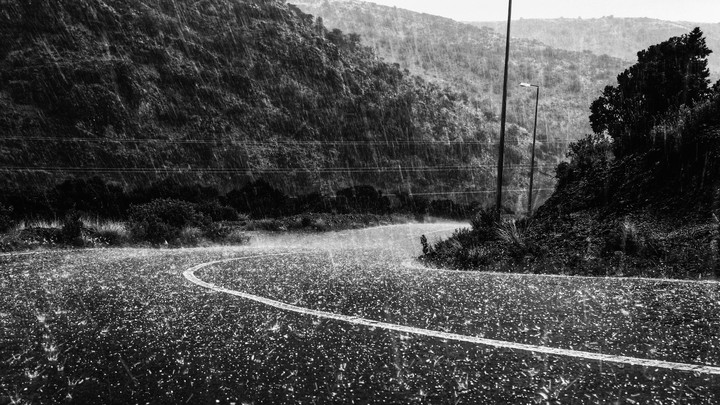 Torrential hail pours down on a winding mountain road