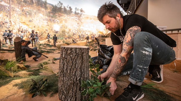 A worker puts some final touches on the diorama that is part of the Atlanta Cyclorama display.