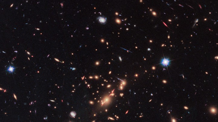A Hubble Telescope image that includes a red, disk-shaped galaxy seen through a gravitational lens in the upper right corner.