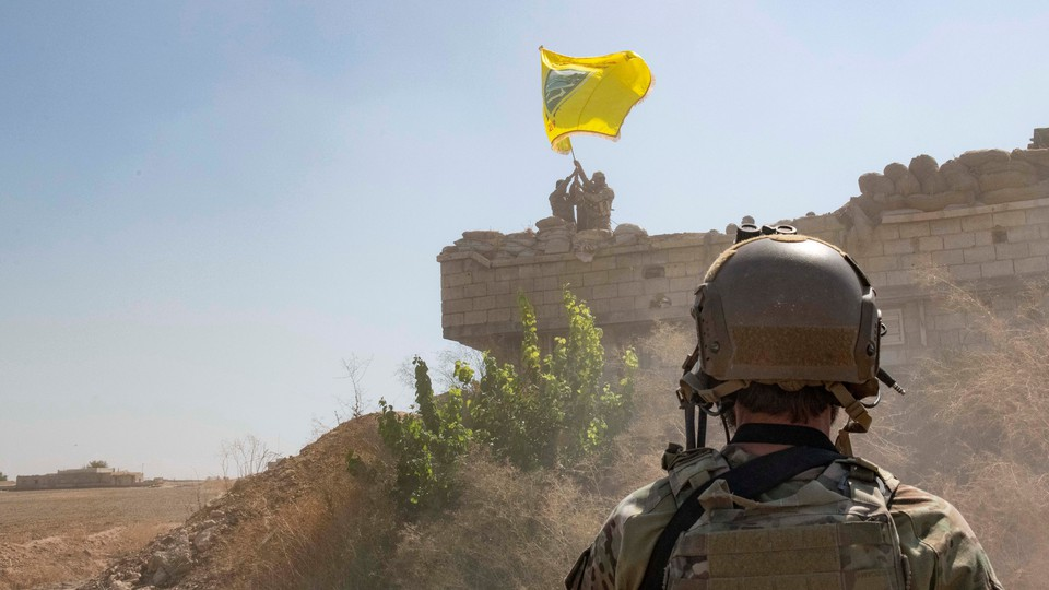 A U.S. soldier watches Syrian Democratic Forces raise a flag in the background.