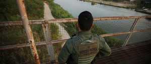 A U.S. border patrol agent looks over the Rio Grande river at the border between United States and Mexico, in Roma, Texas.
