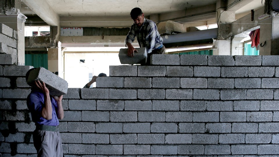 Two workers lay stones in order to rebuild a shop that was destroyed during fighting between Iraqi forces and Islamic state fighters in Mosul, Iraq.