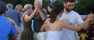 A photo of couples dancing in a park.