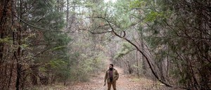 """In a promotion for the podcast """"S-Town,"""" a man stands in the woods."""