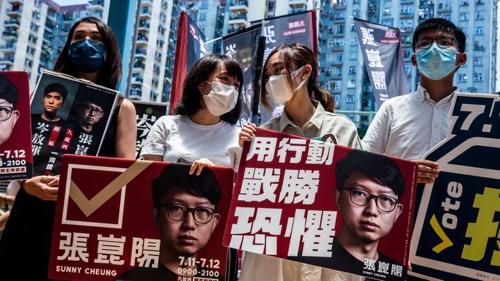 Prodemocracy activists hold signs in Hong Kong.