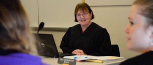 A judge in her robe sits at a desk facing two women whose backs are to the camera.