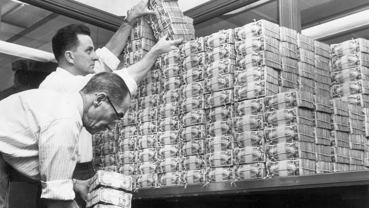 Men stacking bundles of money.