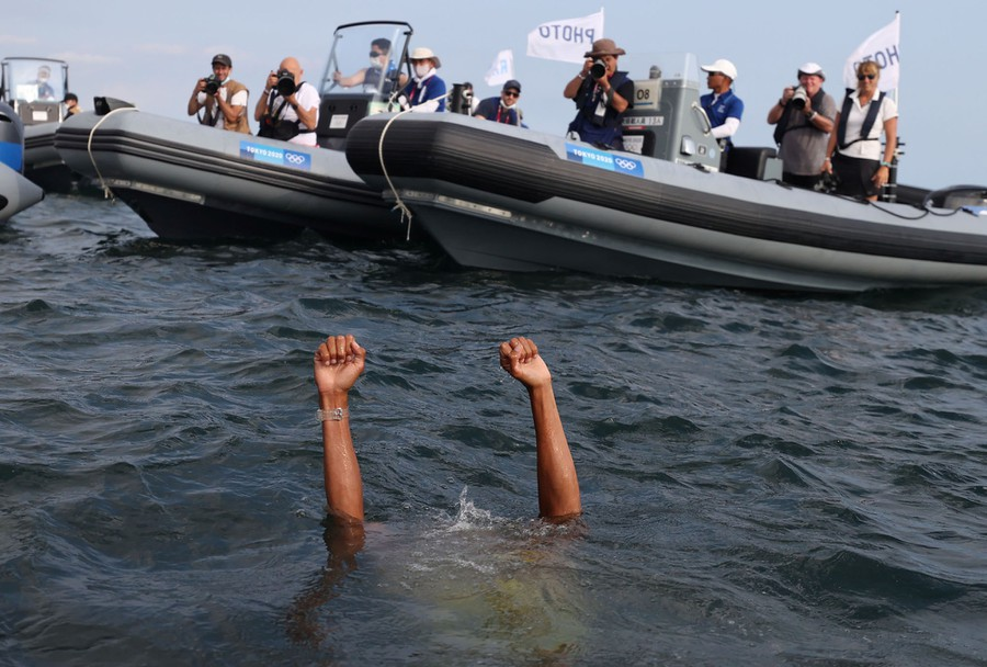 Two arms rise from harbor water as a person celebrates a win while mostly underwater, surrounded by press and support boats.