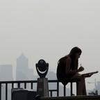 a girl works on a drawing amid a smoky haze