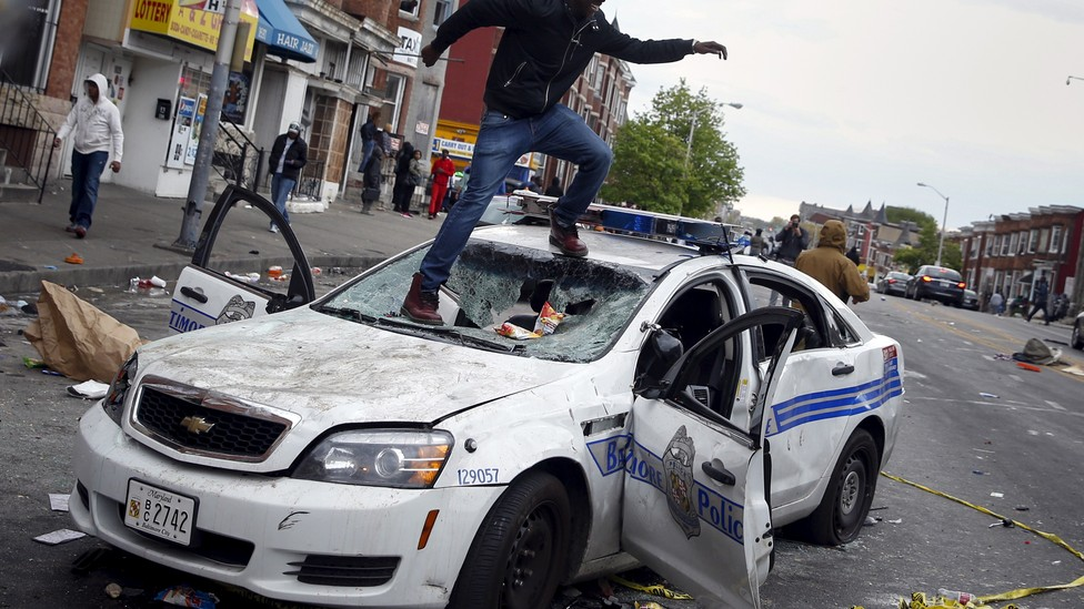 A man jumps on a destroyed Baltimore Police car during protests after the death of Freddie Gray.