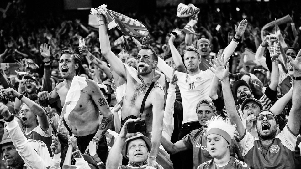 Black-and-white photo of Denmark's fans celebrate the team's victory after defeating Russia in a match