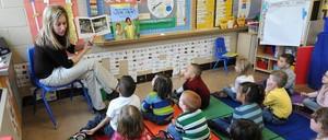 Preschool students listen to their teacher, Angie Clark, read at a Des Moines Iowa elementary school.