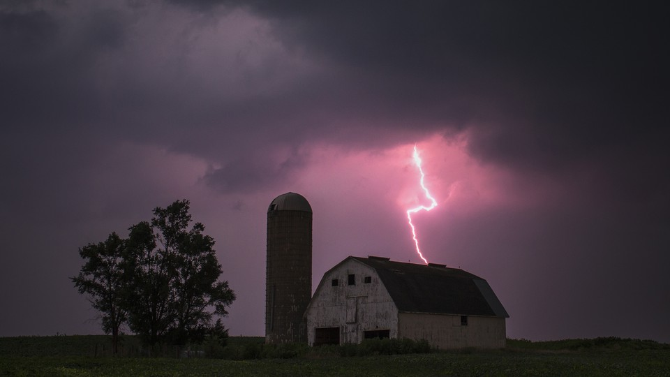 An image of a barn, with lightning striking over it.
