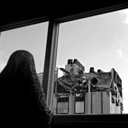 A woman looks through a window at the rooftop of a building which was hit by an airstrike.