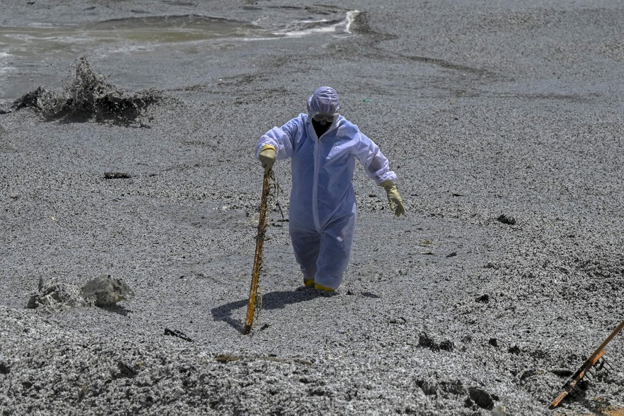 A Navy member in protective gear wades through seawater and plastic debris.