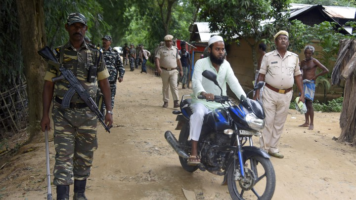 Indian security officers patrol a dirt road as a man rides past them on a motorcycle.