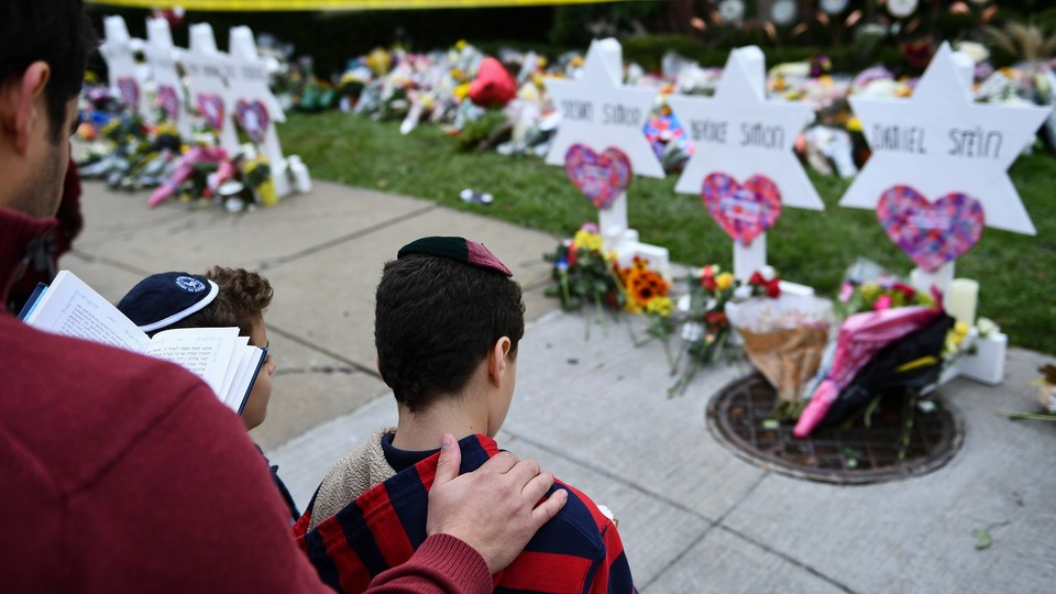 A man places his hand on the back of a boy while standing in front of a memorial.