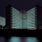 Modernist housing towers at night.