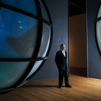 Mel Chin, standing with his work  Sea to See, two large glass blue globes.