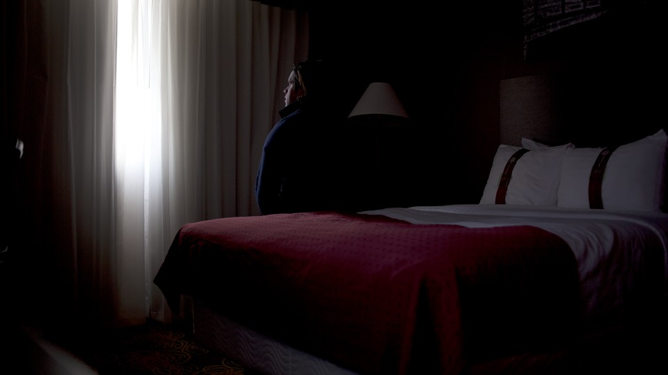 A young man sits on a hotel-room bed, alone, and looks out the window.