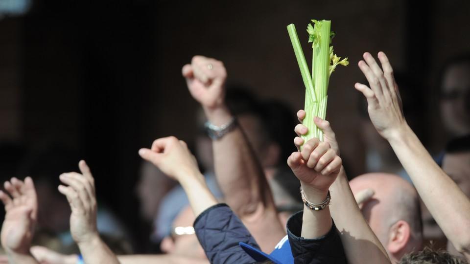A man in a crowd holds a stalk of celery aloft.