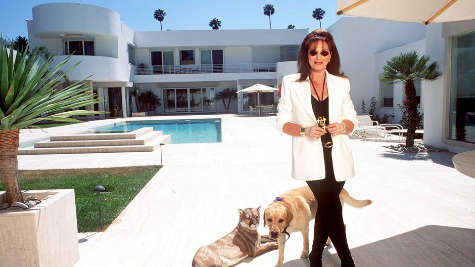 The author Jackie Collins standing by a pool, surrounded by palm trees
