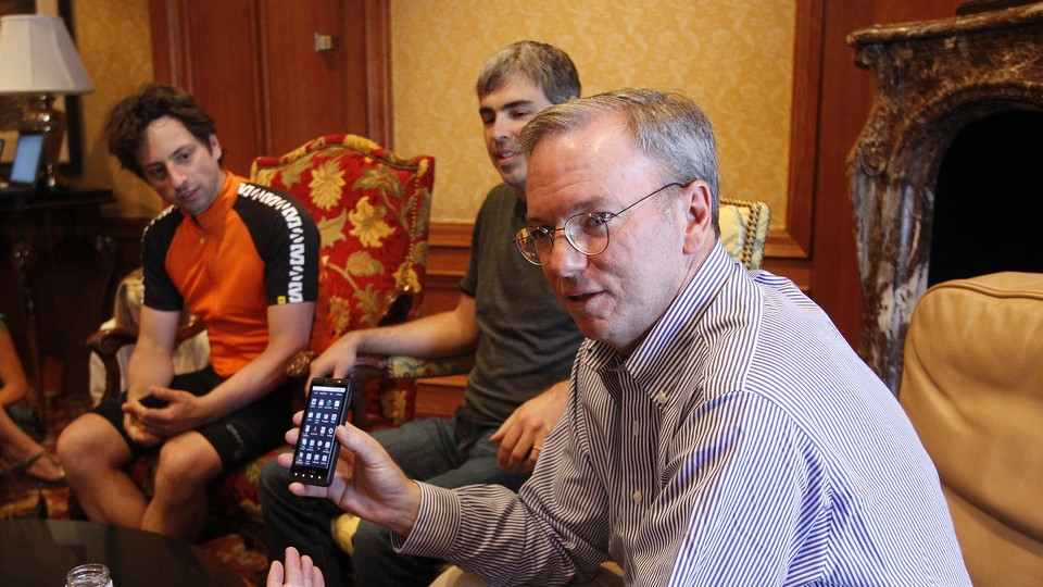One man holds up an Android phone while two others look on.